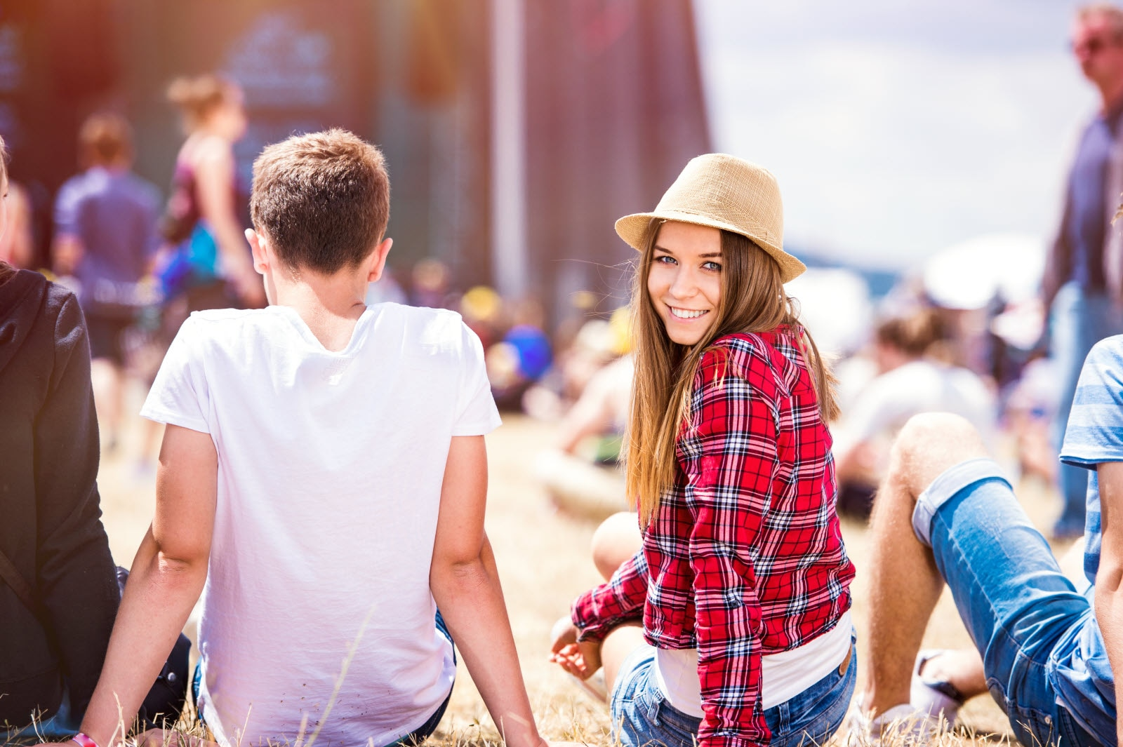 Teenage couple at summer music festival, sitting in front of stage