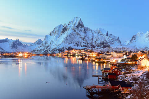 Winter in Reine, Lofoten Islands. The lights from the city are bright in the evening.