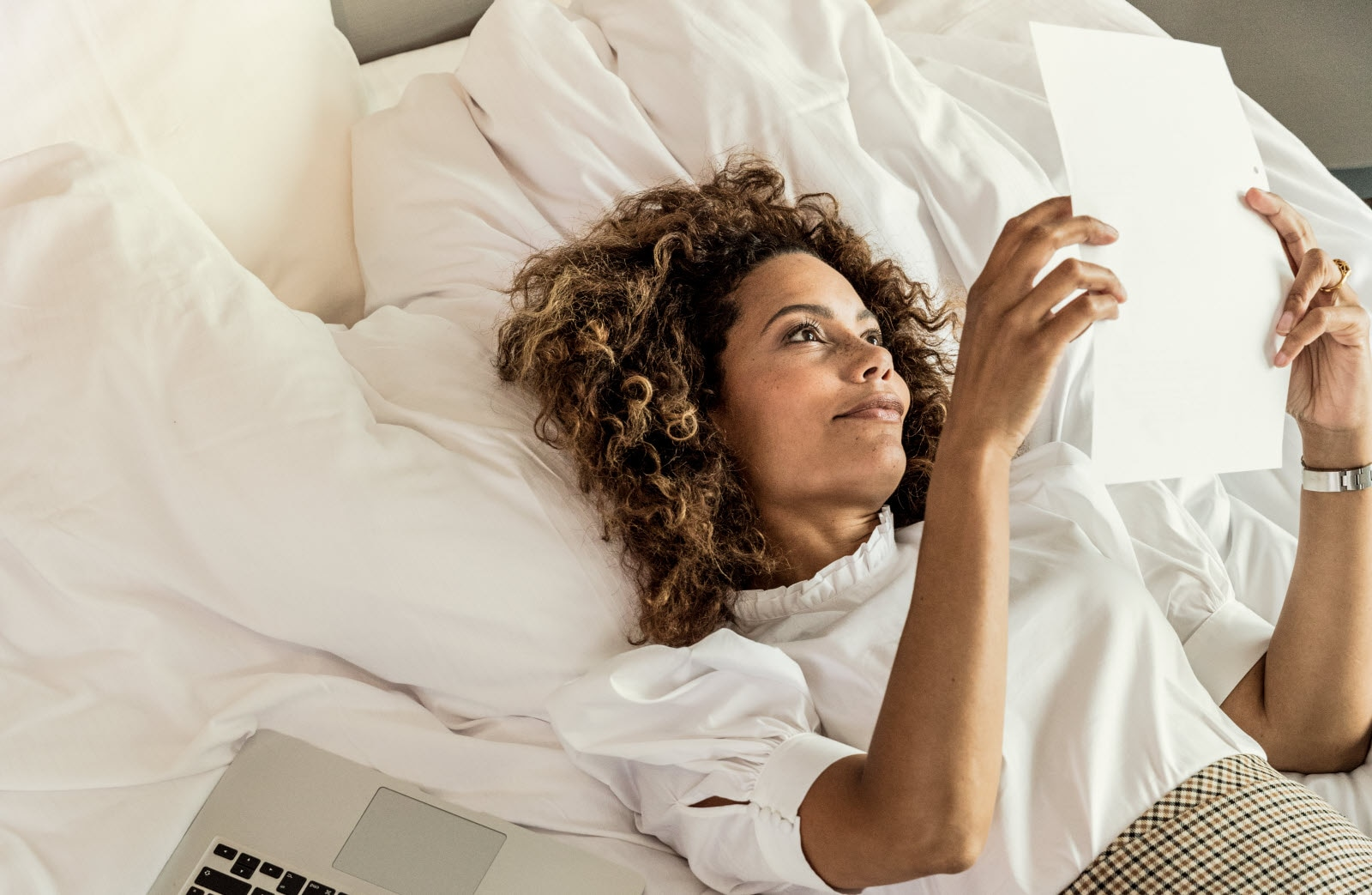 Woman working in bed