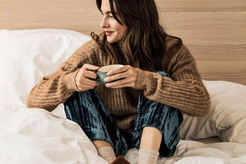 Woman having coffee sitting on the bed