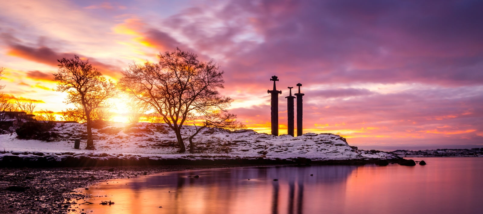 Beautiful sunrise in the back of the snowy monument, 3 swords outside of Stavanger